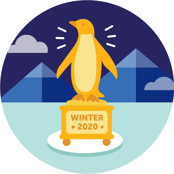 Golden Penguin Statue in front of snowy mountains