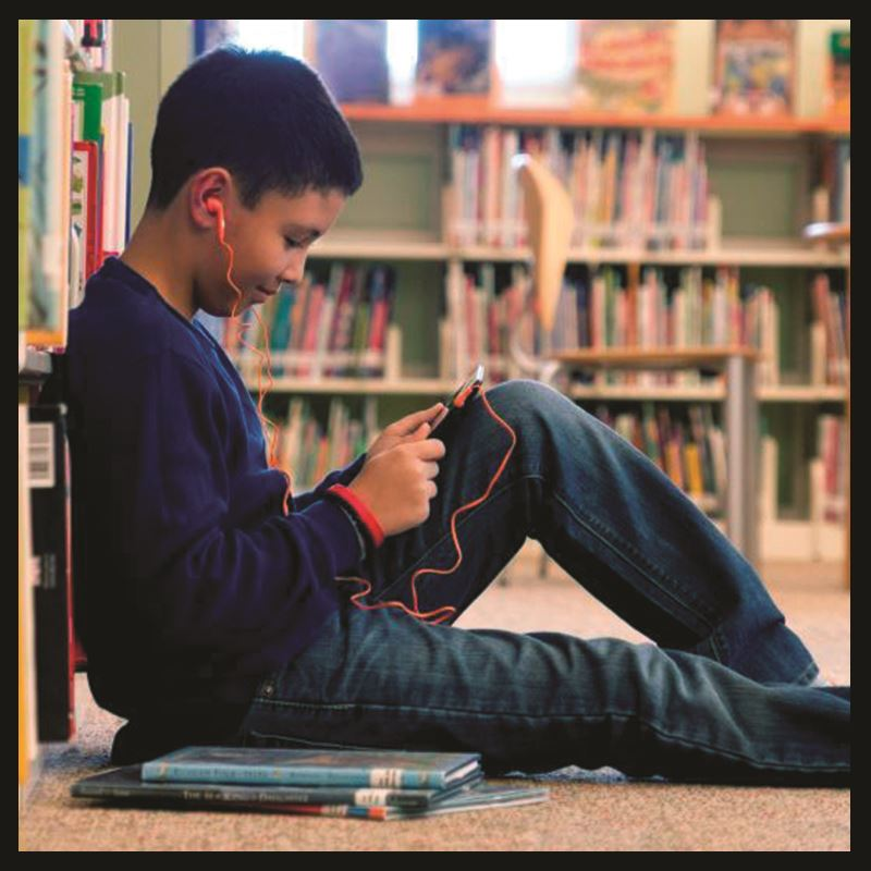 Read young boy listing to audiobook sitting on floor of library