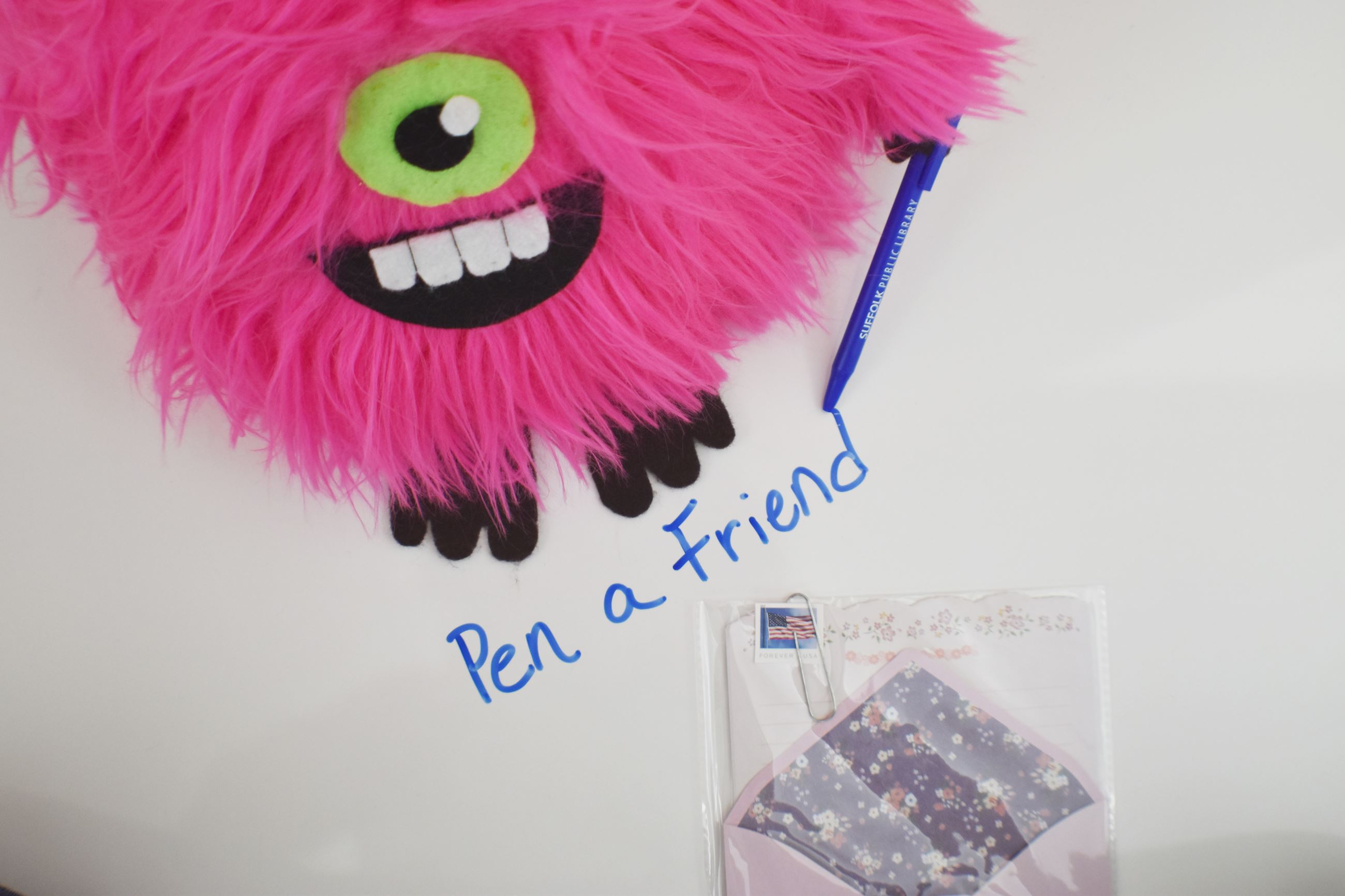 Stuffed pink furry  monster with pen, stationary and stamp