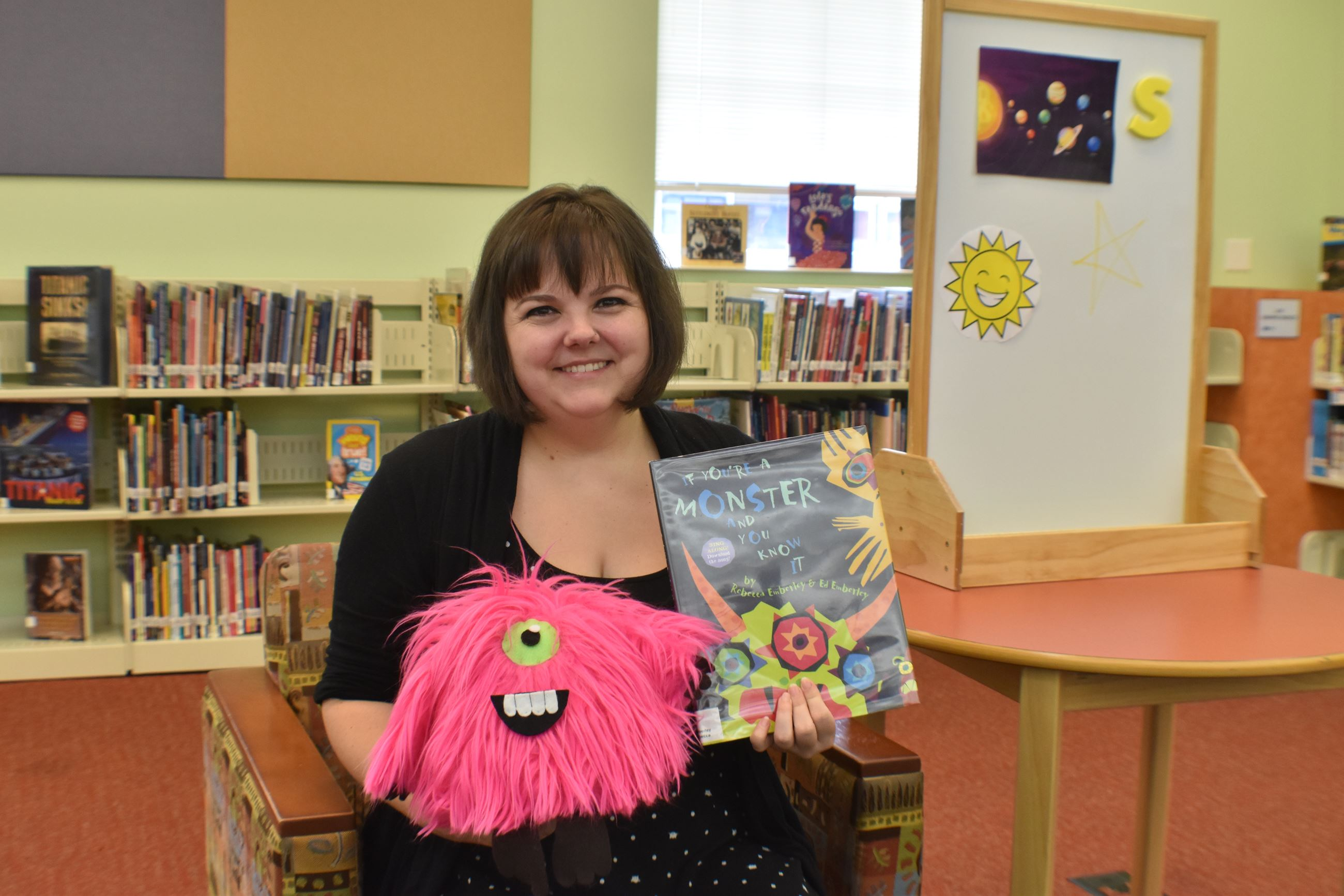 Library staff holding book and pink stuffed monster Fred in front of bookshelves
