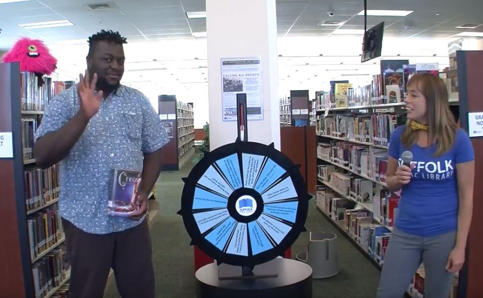 Still shot of Face the Wheel video of man holding book next to a wheel and female host