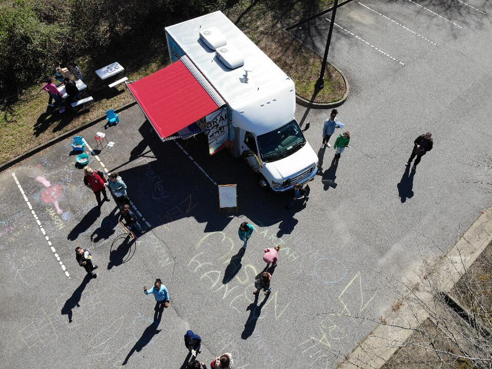 Aerial view of Library2Go vehicle in parking lot surrounded by people